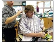 Bowling for Columbine movie still: Michael Moore gets his hair cut by Chip Smith at a babershop where you can also buy bullets in Bowling for Columbine